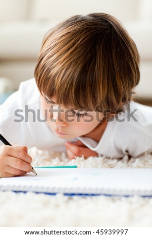 Adorable little boy drawing lying on the floor in the living-room