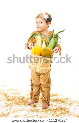 adorable little boy dressed as a Native American holding a basket of harvest vegetables - stock photo