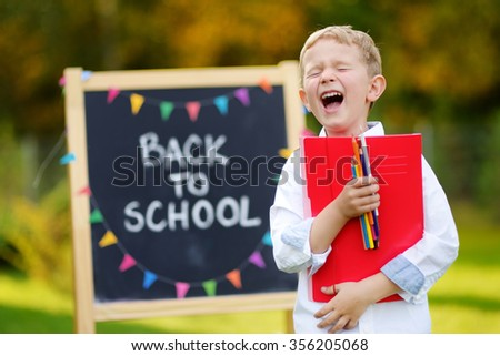 Adorable little boy feeling very exited about going back to school - stock photo