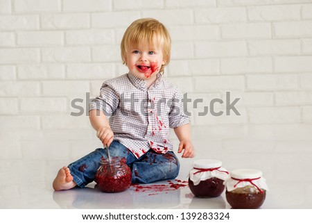 Adorable little boy got messy eating strawberry jam from glass jars - stock photo
