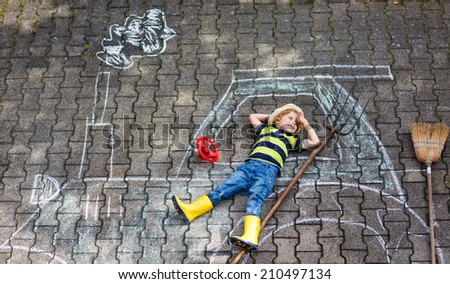 Adorable little boy having fun with tractor picture drawing with chalk. - stock photo
