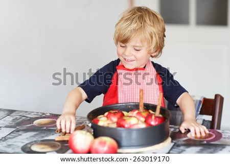 Adorable little boy helping and baking apple pie in home''s kitchen, indoor. - stock photo
