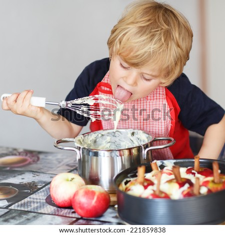 Adorable little boy helping and baking apple pie in home''s kitchen, indoor. Tasting vanilla dough. - stock photo