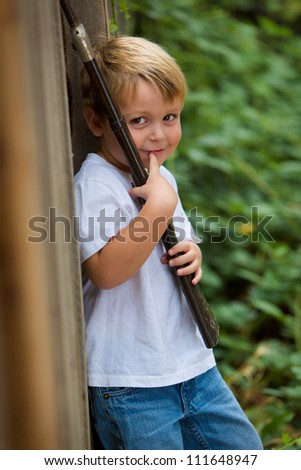 adorable little boy holding a toy rifle and smiling