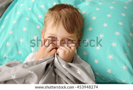 Adorable little boy holding bed sheet in hands - stock photo