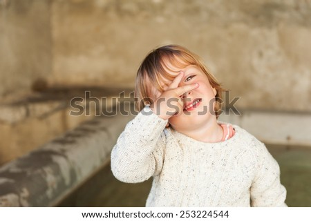 Adorable little boy looking through his fingers - stock photo