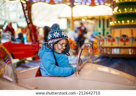 Adorable little boy on a carousel at Christmas funfair or market, outdoors - stock photo