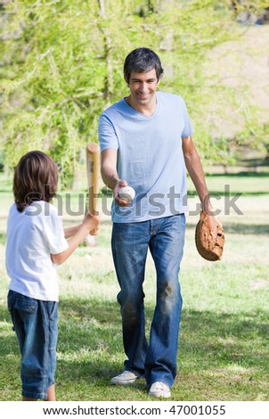 Adorable little boy playing baseball with his father in the park - stock photo