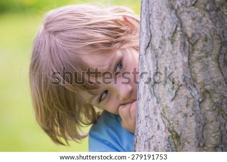Adorable little boy playing hide and seek hiding behind a  tree trunk in the green summer park