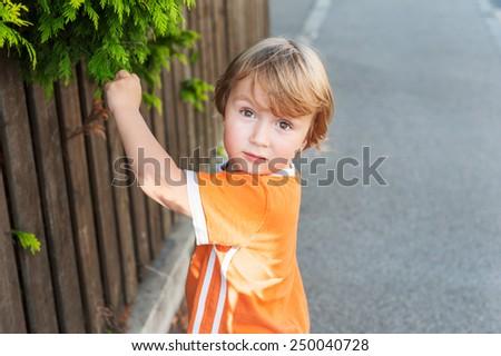 Adorable little boy playing in a neighborhood - stock photo