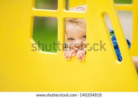 Adorable little boy playing on playground at park. Soft focus on eyes.  - stock photo