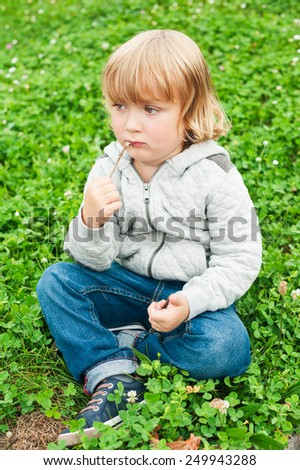 Adorable little boy playing outdoors - stock photo