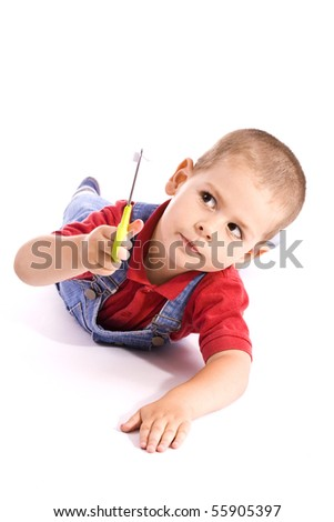 adorable little boy playing whit scissors