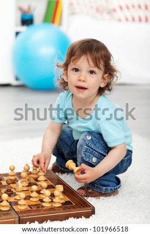 Adorable little boy playing with chess pieces indoors - stock photo