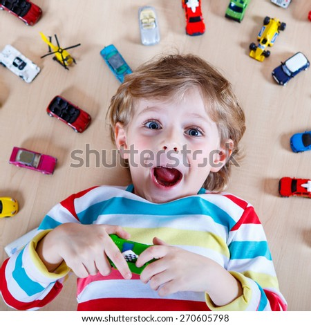 Adorable little boy playing with lots of toy cars indoor. Child wearing colorful shirt and having fun. - stock photo