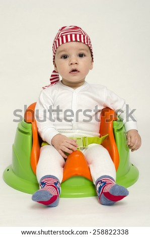 Adorable little boy relaxing in a toy chair ready for his dinner. Baby looking curious with big eyes and open mouth. Playful kid dressed as a pirate - stock photo