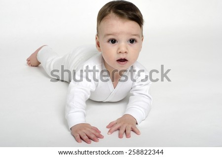 Adorable little boy relaxing in white sheets after a bath. Baby looking curious with big eyes and open mouth - stock photo