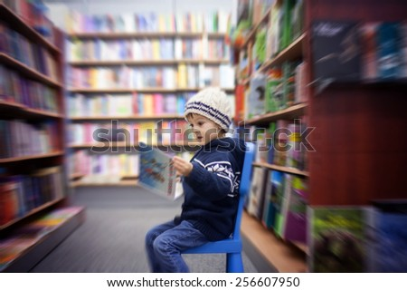 Adorable little boy, sitting in a book store, looking at books, radial blur - stock photo