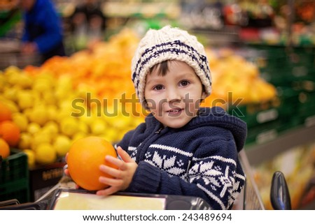 Adorable little boy, sitting in a shopping cart, holding oranges - stock photo