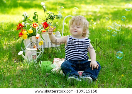 Adorable little boy sitting on the green grass with his eyes closed surrounded with flowers and soap bubbles