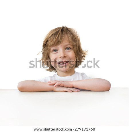 Adorable little boy smiling on white table edge isolated over white background
