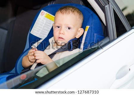 Adorable little boy wearing waiting in a car strapped into a child safety seat and peering out of the open passenger window - stock photo