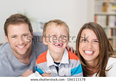 Adorable little boy with a happy grin and missing front teeth sitting between his laughing happy young parents in a beautiful loving family portrait - stock photo