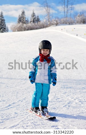 Adorable little boy with blue jacket and a helmet, skiing wintertime
