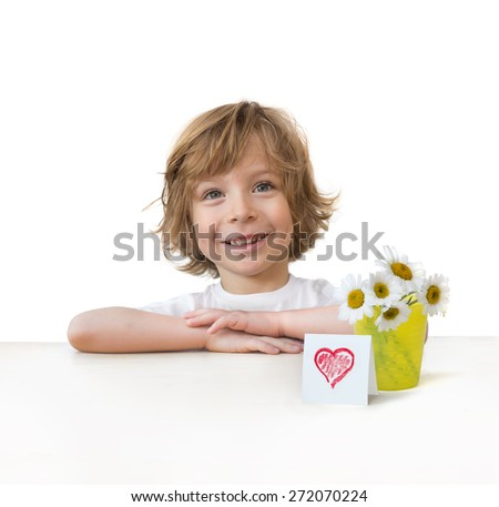 Adorable little boy with daisy bouquet and a red heart card on the table edge isolated over white background