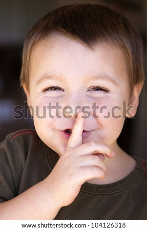 Adorable little boy with finger to his lips signaling for quiet