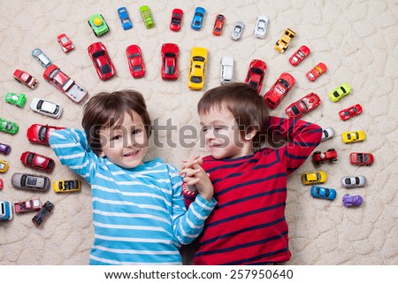 Adorable little caucasian boys with striped shirts, lying on the ground, red, yellow, blue and white toy cars around him , looking and smiling at the camera, shot from above