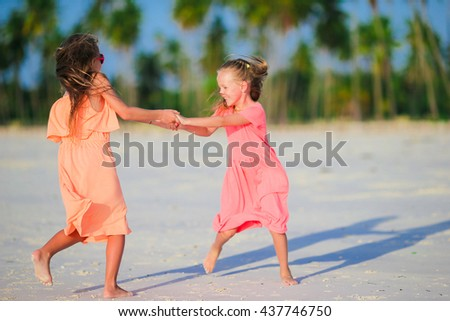 Adorable little caucasian girls at beach during summer vacation. Happy kids having fun together on their family summer vacation. - stock photo