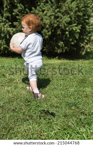 Adorable little child boy with soccer ball in park on nature at summer. Use it for baby, parenting or love concept - stock photo