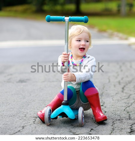 Adorable little child, cute blonde toddler girl learning to ride and balance on push scooter on the street in the countryside - stock photo