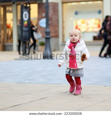 Adorable little child, cute blonde toddler girl wearing warm padded jacket walking during winter sales period in the city shopping street decorated for Christmas, eating warm waffle - stock photo