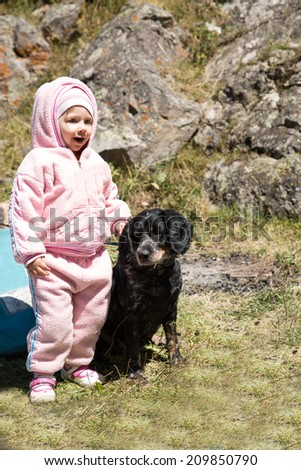 Adorable little child girl playing with pet dog outdoor in park. Summer green nature background.  Use it for baby, parenting or love concept - stock photo