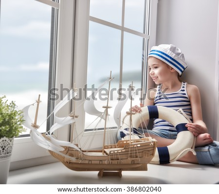 Adorable little child girl sitting on the window and holding lifeline. Girl looks at the blue sky and dreams of sea, adventures and travel. Girl has a toy ship. - stock photo