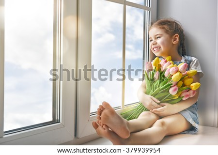 Adorable little child girl sitting on the window and holding tulips. Girl looks at the blue, pure sky and rejoices to spring and sun. - stock photo