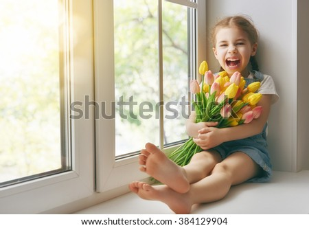 Adorable little child girl sitting on the window and holding tulips. Girl rejoices to spring and sun. - stock photo