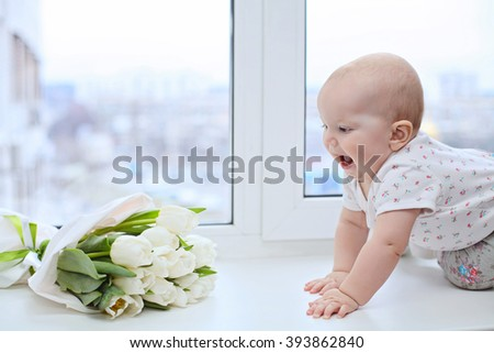 Adorable little child girl sitting on the window and holding white tulips. Girl looks at the blue, pure sky and rejoices to spring and sun. concept of celebraiting spring holiday or birthday  - stock photo