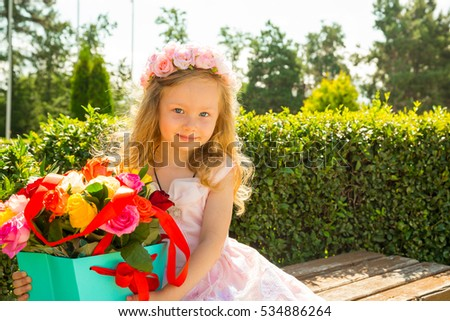 Adorable little child girl with bouquet of flowers on happy birthday. Summer green nature background. Use it for baby, parenting or love concept