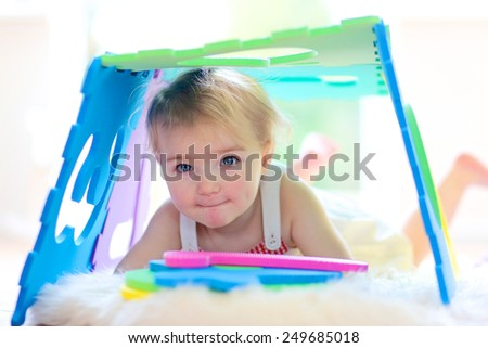 Adorable little child, happy blonde toddler girl playing hide and seek and learning numbers with colorful soft puzzles lying on the floor at home or kindergarten - stock photo