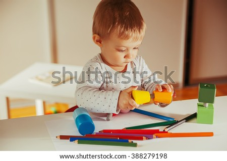 Adorable Little Child Playing With Colorful Plastic Toys Indoors - stock photo