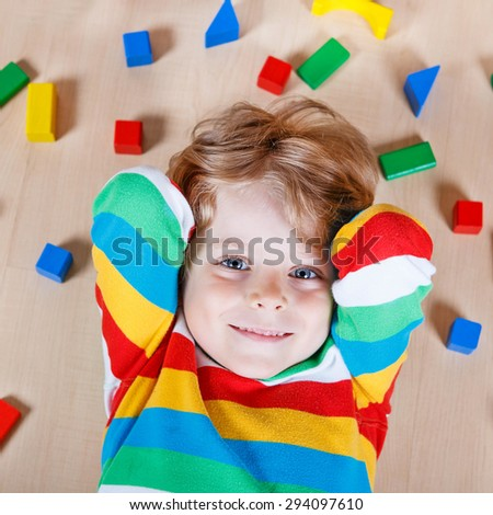 Adorable little child playing with lots of colorful wooden blocks indoor. Active kid boy wearing colorful shirt and having fun with building and creating. - stock photo