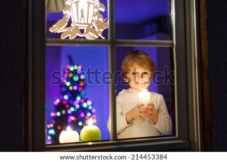 Adorable little child waiting for Santa by window at Christmas time and holding candle. With colorful lights from Christmas tree on background, selective focus. - stock photo