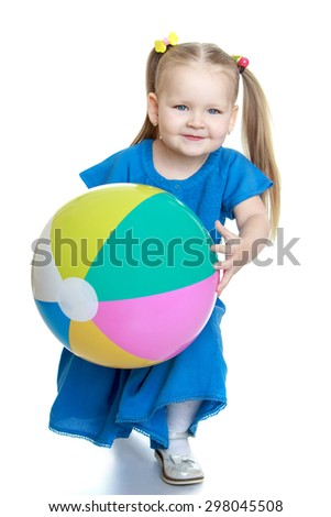 Adorable little chubby blonde girl in a blue summer dress holding a large inflatable striped ball-Isolated on white - stock photo