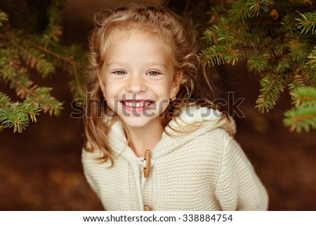 Adorable little curly blond girl in beige knitted sweater smiles broadly, sitting on a background of green fur-trees, autumn - stock photo