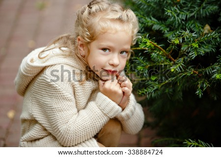 Adorable little curly blond girl in beige knitted sweater smiles slyly, on a background of green fur-trees and house in autumn - stock photo