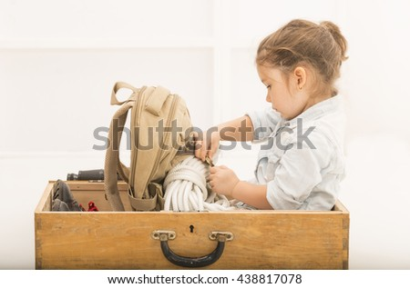 Adorable little explorer girl in a safari hat and explorer clothes playing Safari sitting in a old wooden suitcase with backpack and safety rope. Getting ready for the summer vacation - stock photo