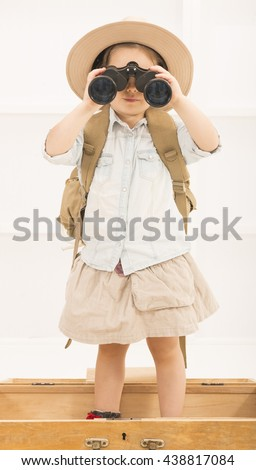 Adorable little explorer girl in a safari hat and explorer clothes with binoculars playing Safari sitting in a old wooden suitcase. Little child playing treasure hunt. Looking for the summer vacation - stock photo